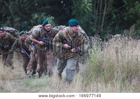 WESTERNHANGER, UK - JULY 24: British commandos use scrub cover as they advance on German positions during the main battle re-enactment at the War & Peace revival show on July 24, 2015 in Westernhanger