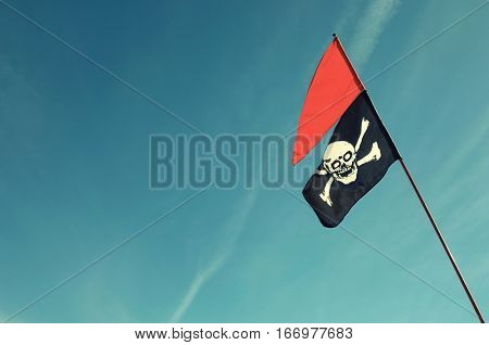 Skull and cross bones flag against blue sky