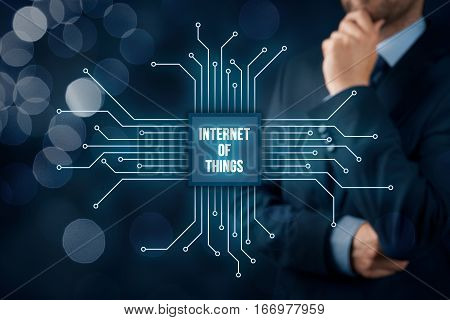 Internet of things (IoT) concept. Businessman think about Internet of Things (IoT). Abstract chip connected with abstract devices represented by points.