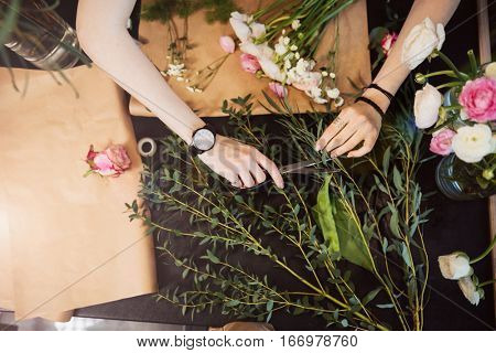 Top view of hands of young woman florist cutting flowers with scissors and designing bouquet on black table