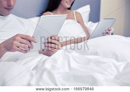 people, bedtime, technology and relations concept - close up of smiling couple in bed with tablet pc computers