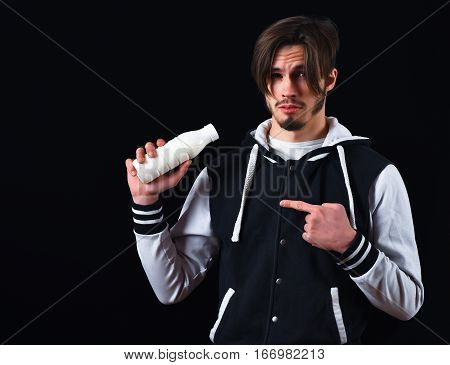 sportive handsome bearded guy in baseball jacket and serious face holding kefir or yogurt in studio on black studio background