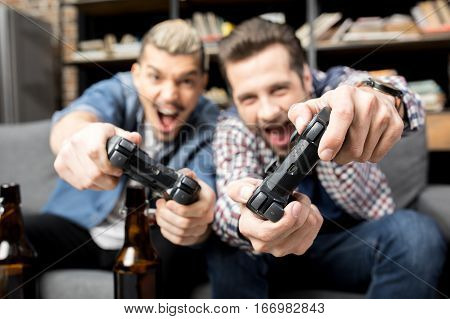 Close-up view of young emotional men playing with joysticks on couch