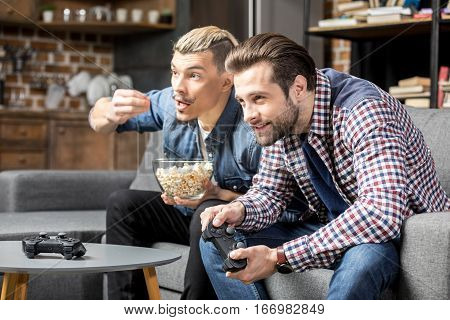 Two young men playing with joysticks and eating popcorn