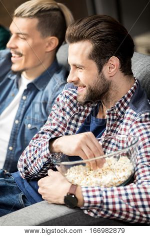Smiling male friends sitting on couch and eating popcorn