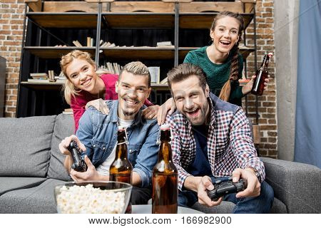 Young smiling friends sitting on couch and playing video games with joysticks