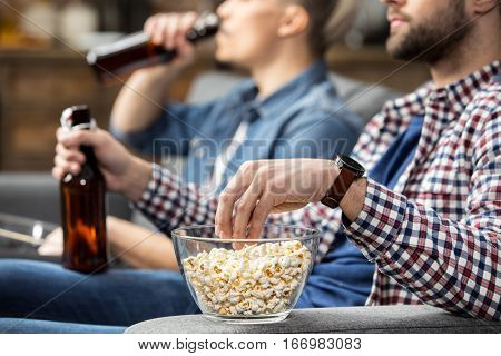 Close-up partial view of young friends eating popcorn and drinking beer