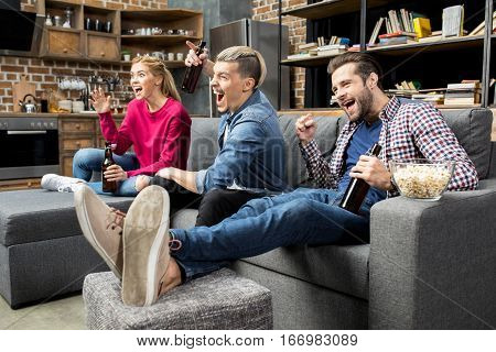 Young excited male and female friends drinking beer on couch