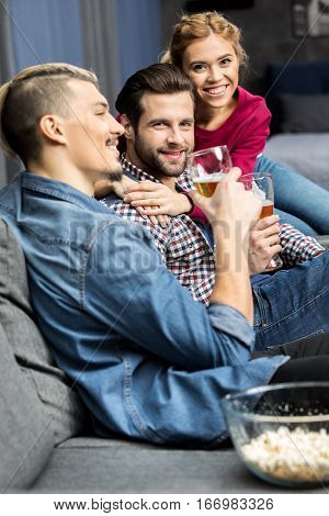 Happy young friends sitting on couch and drinking beer