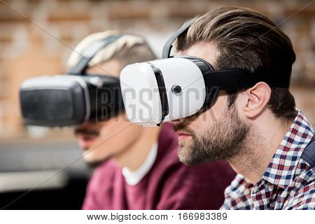 Side view portrait of two young men in virtual reality glasses