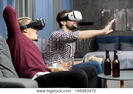 Two men in virtual reality glasses sitting on sofa and eating popcorn