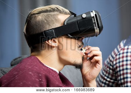 Young man in wirtual reality glasses eating popcorn
