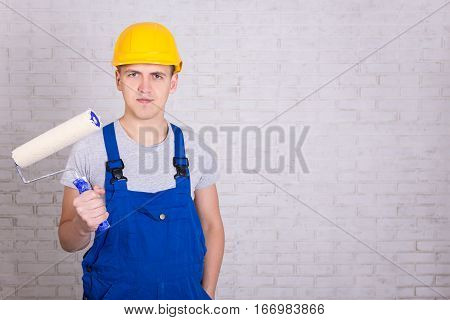 Young Man Painter In Workwear With Roller Paintbrush Over White Wall