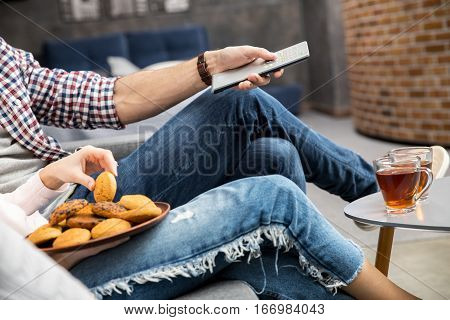Couple eating biscuits and drinking tea while watching tv