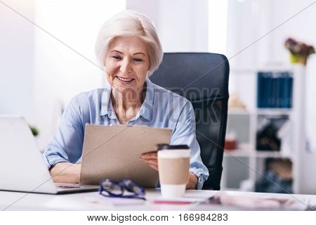 Delighted from my responsibilities. Charming smiling aged businesswoman sitting at the table in the office in front of the laptop and holding the document table while expressing positivity