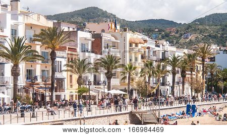 Sitges Spain - May 26 2013 - View of the Port Alegre street in front of the beach full of tourists in the village of Sitges Spain