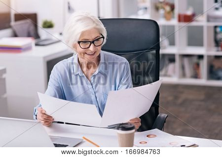 Business papers in my hands. Involved cheerful senior businesswoman sitting at the table at the workplace and holding business papers while expressing positivity and reading