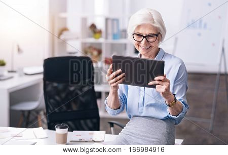 Modern gadgets in use. Joyful smiling aged businesswoman standing in the office and holding the tablet while expressing gladness