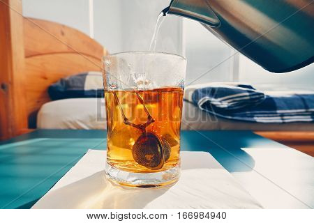 Hot tea in glass cup on the bedside table in bedroom.