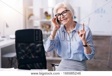 Listen to my idea. Cheerful smiling senior woman standing in the office and holding the phone while enjoying conversation and showing the forefinger up