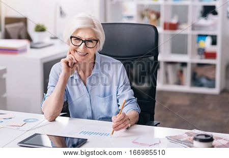 Enjoying my responsibilities. Happy charming aged businesswoman sitting at the table in front of the tablet in the office and holding the pencil while expressing joy and working on the project