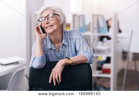 Delighted from conversation. Cheerful involved aged woman standing near the chair in the office and holding the mobile while expressing positivity and having the conversation