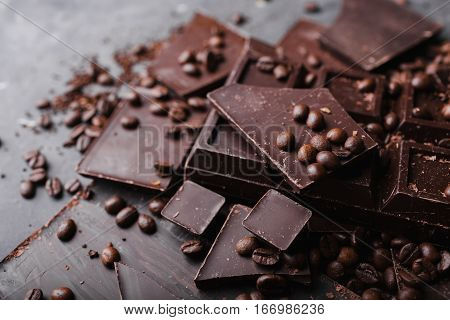 Chocolate and coffee beans. Large bar of chocolate on gray abstract background. Background with chocolate. Sweet food photo concept. Copyspace