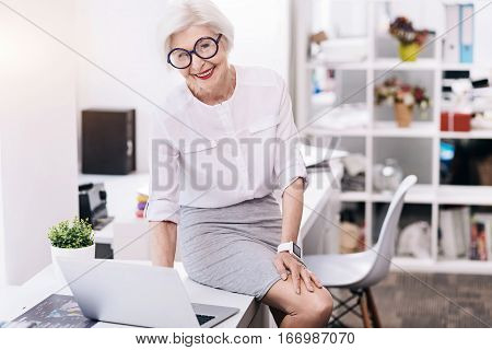 My joyful working hours. Smiling merry senior business lady sitting on the table in the office and using the laptop while working and expressing joy