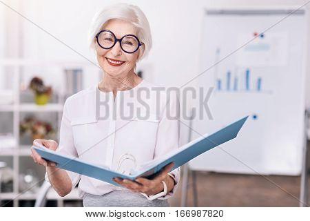 Happy from working in this company . Delighted happy glad businesswoman standing in front of the white board in the office and holding the document folder while smiling