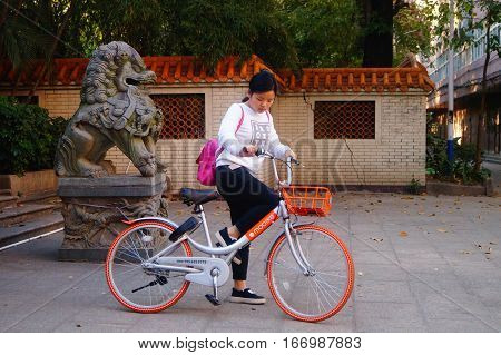 Shenzhen, China: on January 27th, a woman rides a bicycle past the gate of the park on the side of the stone lion, on. In Shenzhen, china.