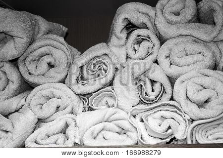 Many White Rolled Towels On A Shelf