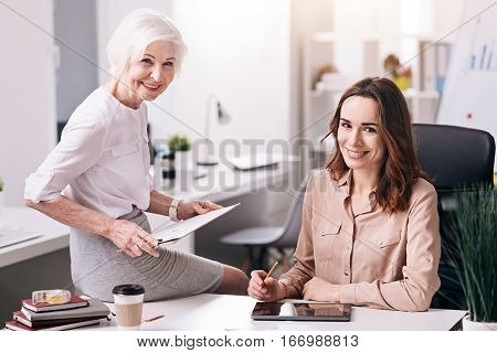Enjoyable process of working together. Smiling glad involved colleagues sitting in the office and working with the tablet and the clipboard while expressing happiness