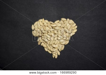 Sunflower seeds in the form of heart. White sunflower seeds on a black background. A lot of white seeds