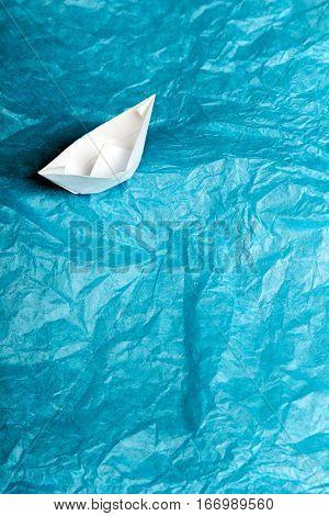 paper ship in blue tissue paper - children's idea of the ship at sea