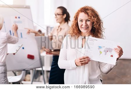 My strategy for successes. Glad positive cheerful businesswoman expressing happiness and standing in the office while holding the paper