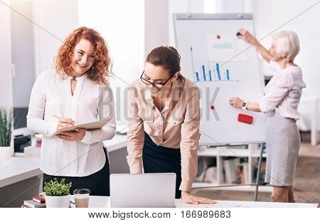 Discussing global trading issues. Glad involved cheerful coworkers standing in the office in front of the laptop and sharing ideas while other colleague writing in the background