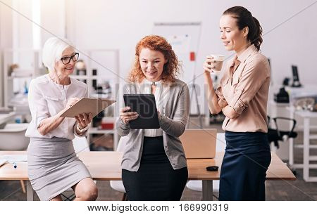 Full of enthusiasm. Diligent hardworking positive businesswomen standing in the office and using the clipboard and the tablet while exchanging opinions
