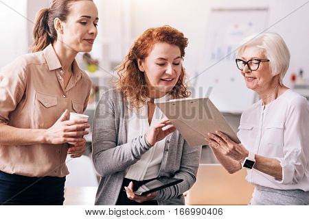 Our brainstorming. Diligent glad involved businesswomen standing in the office and using the clipboard and the tablet while exchanging opinions