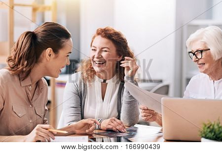 Involved in the conversation. Laughing positive involved businesswomen sitting in the office in front of the laptop and using the documents while exchanging opinions