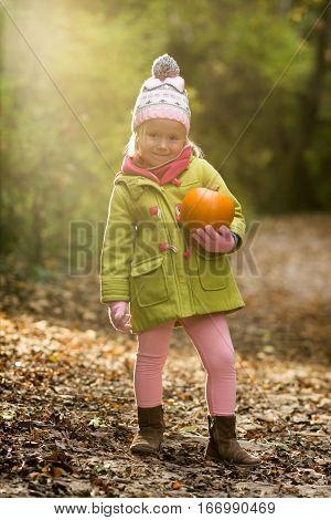 Little Girl Holding A Pumpkin In The Woods