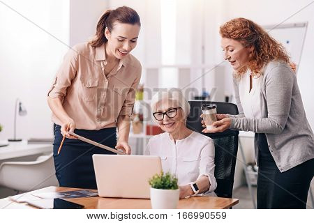 Boss of the company. Smiling positive charming businesswoman sitting in the office in front of the laptop and typing while her subordinates standing and holding clipboard and cup of tea
