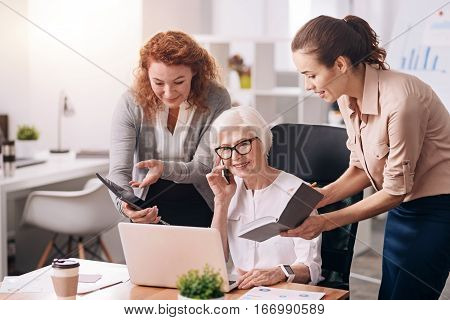 My busy working hours. Pleasant nice charming businesswoman sitting in the office in front of the laptop and talking over the smartphone while her subordinates standing near