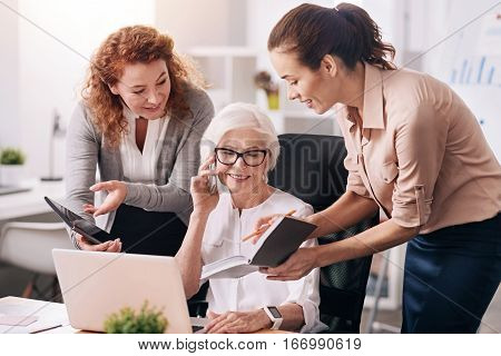 My lovely secretaries. Smiling happy aged businesswoman sitting in the office in front of the laptop and expressing interest while her secretaries standing near and asking