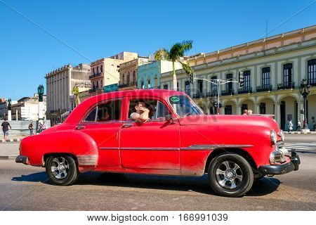 HAVANA,CUBA - JANUARY 24,2017 : A classic red Chevrolet in downtown Havana  on a street sidelined by colorful buildings