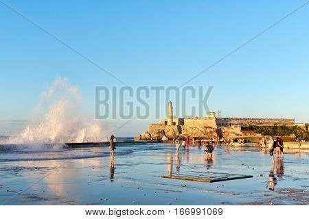 HAVANA,CUBA - JANUARY 24,2017 : El morro lighthouse in Havana with sea waves crashing on the Malecon seawall