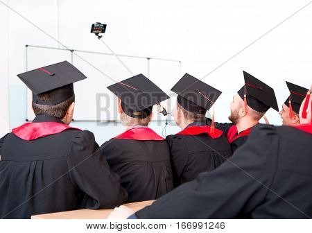 education graduation technology and people concept - group of happy international students in mortar boards and bachelor gowns with diplomas taking selfie in room