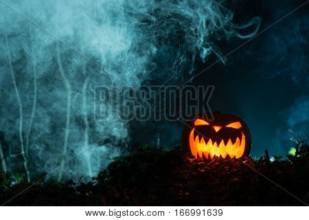 Spooky Gleaming Jack-o-lantern In Dark, Smoky Setting With Copy Space