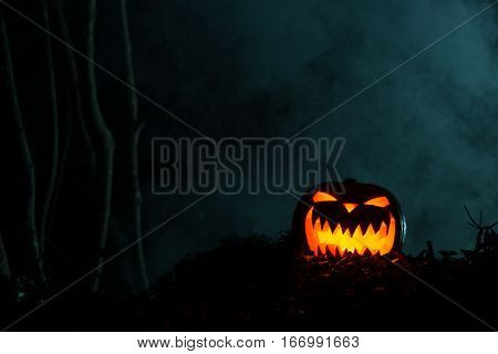 Horrifying glowing jack-o-lantern carved pumpkin in the dark
