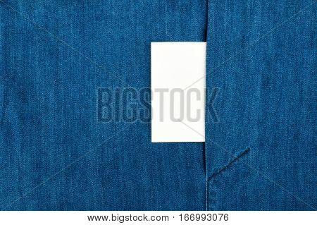 Blank business card with copy space in a pocket of blue jean jacket. View from above