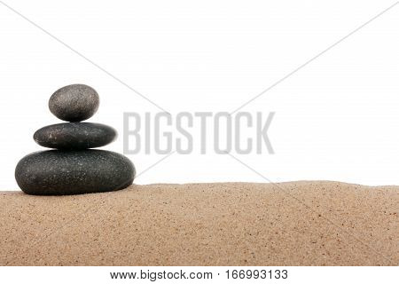 Pyramid of black stones on sand beach. Isolated on a white background. Meditation concentration relaxation harmony balance